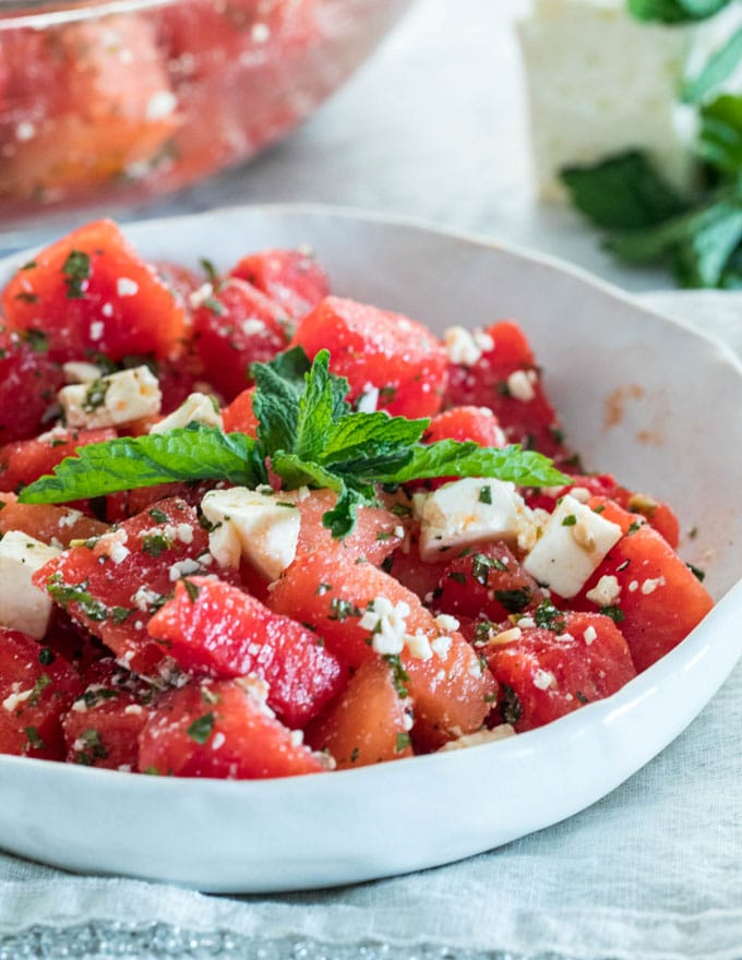 a bowl of watermelon and feta salad with a sprig of mint