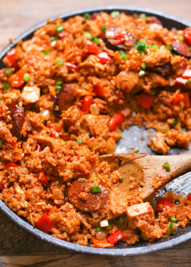 a wooden spoon in a skillet of cajun chicken and sausage rice