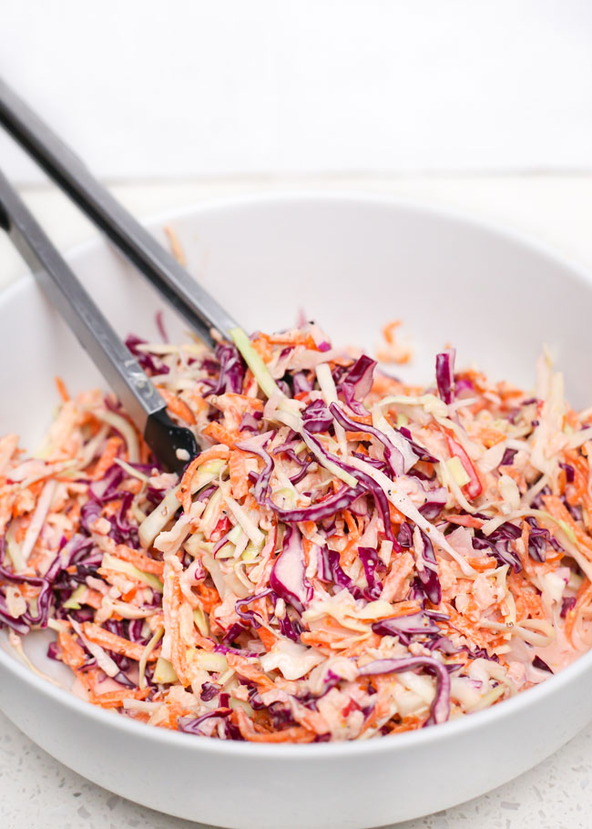 a bowl of apple coleslaw with tongs