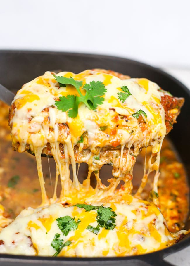 a spatula lifing a cheesy piece of salsa chicken out of a skillet