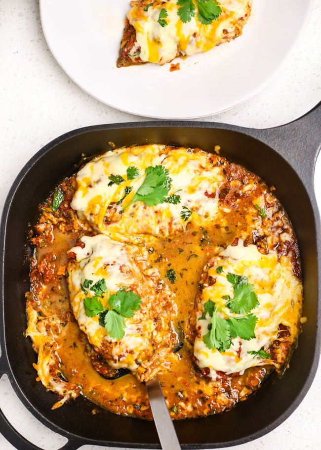 overhead shot of a skillet with cheesy baked salsa chicken