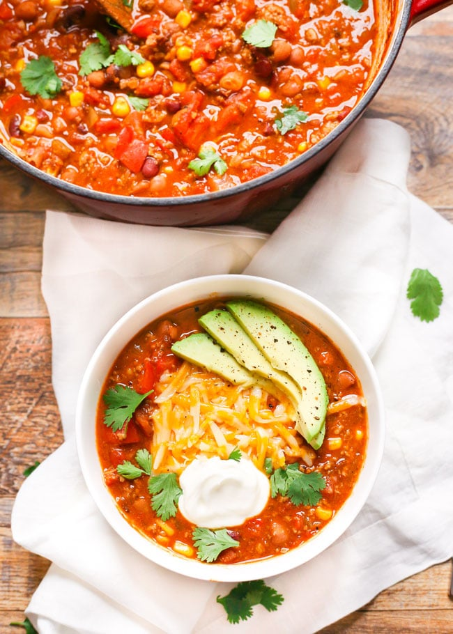 overhead shot of a bowl of turkey chili topped with cheese, cilantro, sour cream, and avocado.