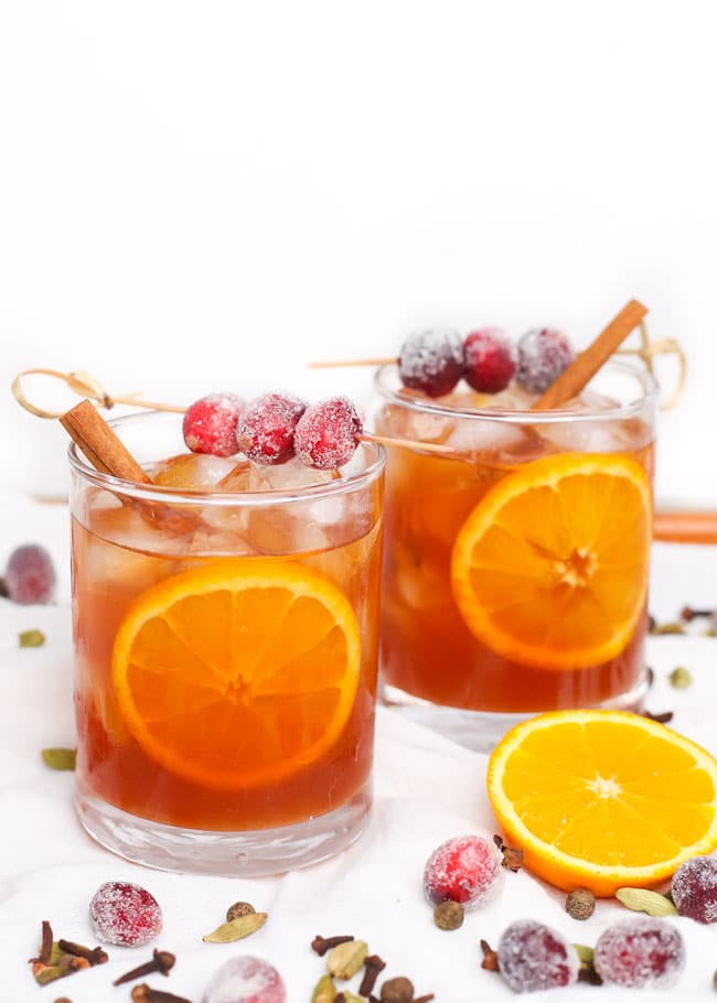 two glasses of cranberry cider garnished with cranberries, orange, and a cinnamon stick.