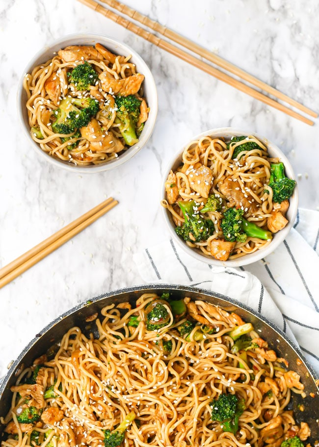 overhead photo of two bowls of chicken broccoli stir fry with wooden chopsticks and a skillet