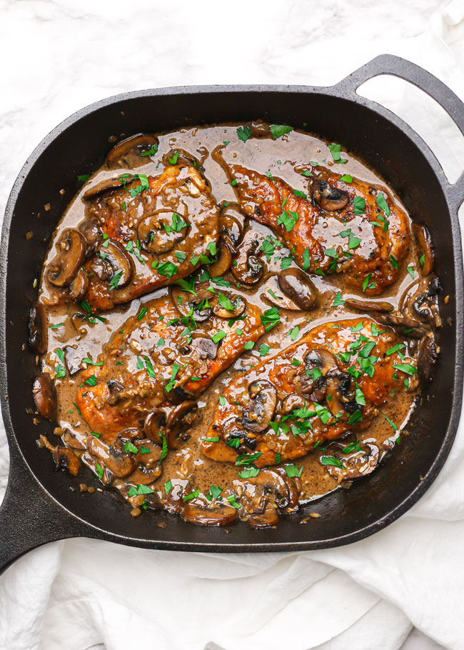 overhead photo of chicken marsala in a skillet with parsley
