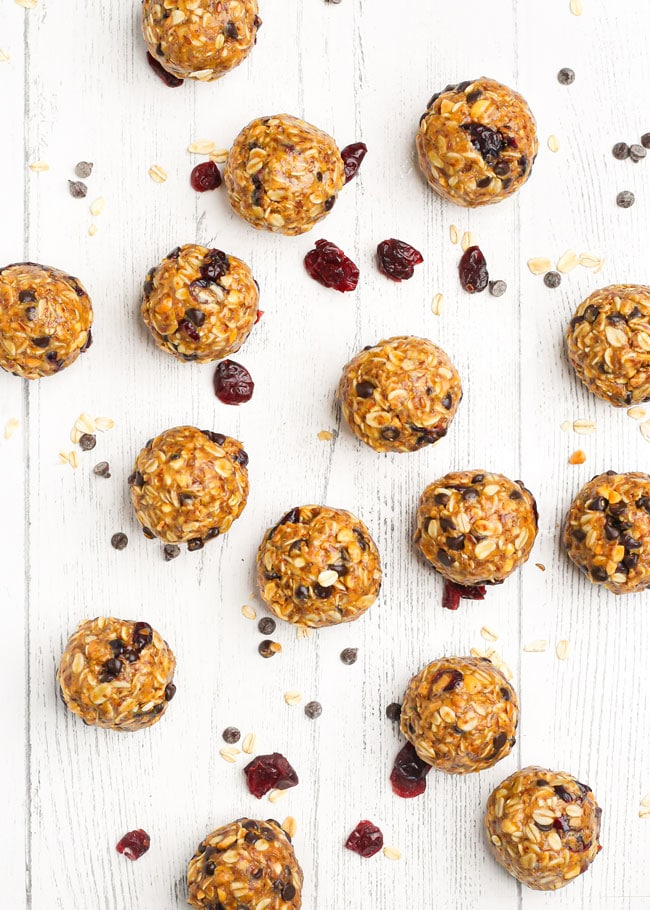 oatmeal energy balls on a table with chocolate chips and dried cranberries