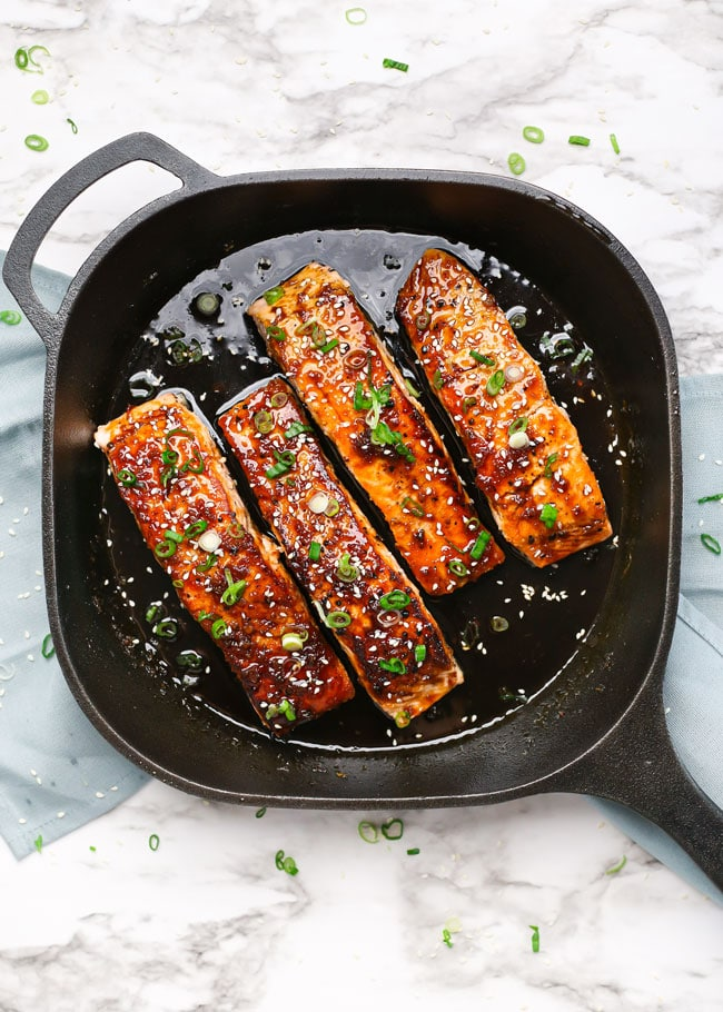 overhead of a skillet with maple soy glazed salmon fillets