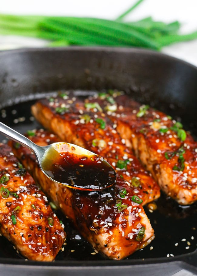 spooning maple soy glaze over a salmon fillet