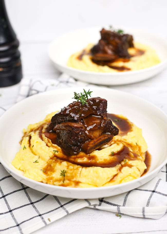 a plate with a short rib over polenta with sauce