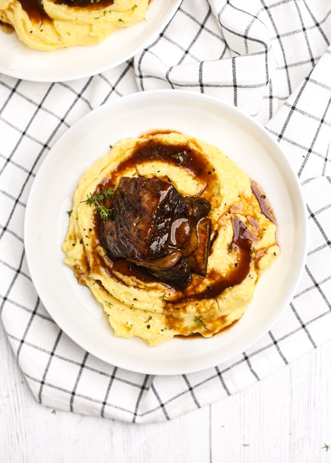 overhead shot of a plate with a short rib over polenta with sauce