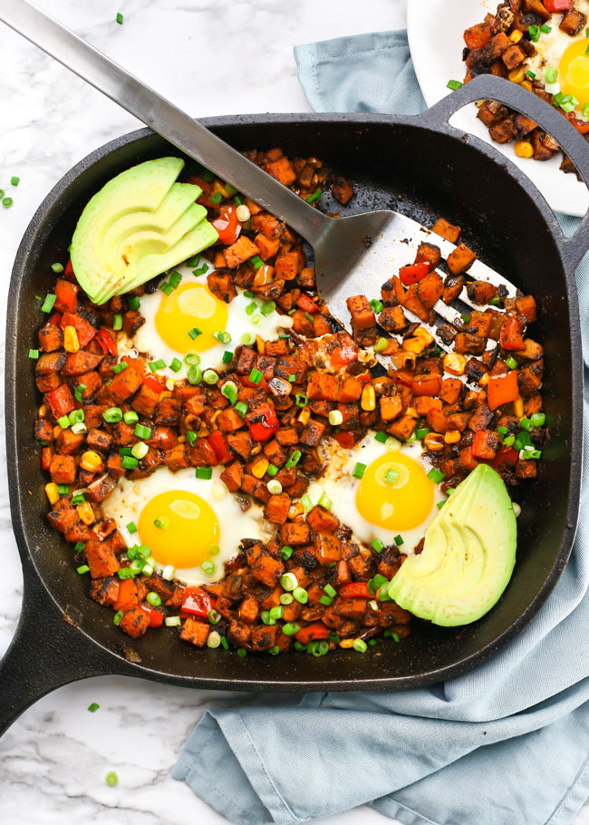 Overhead photo of a sweet potato breakfast hash topped with eggs, avocado, and green onion