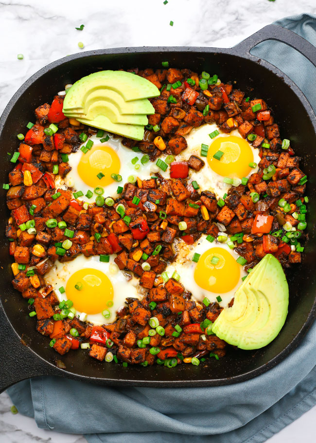 overhead photo of a sweet potato hash topped with eggs and avocado
