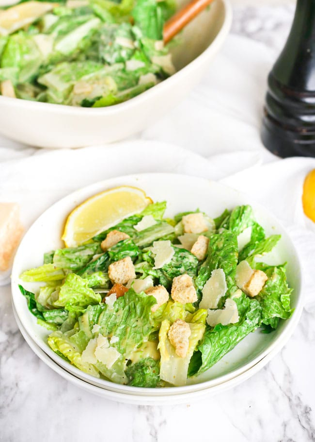 a plate of caesar salad with a lemon wedge