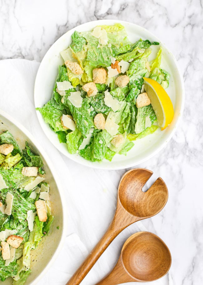 overhead photo of a plate with caesar salad with a lemon wedge