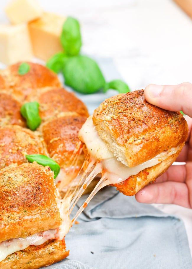 holding up a cheesy chicken parmesan slider