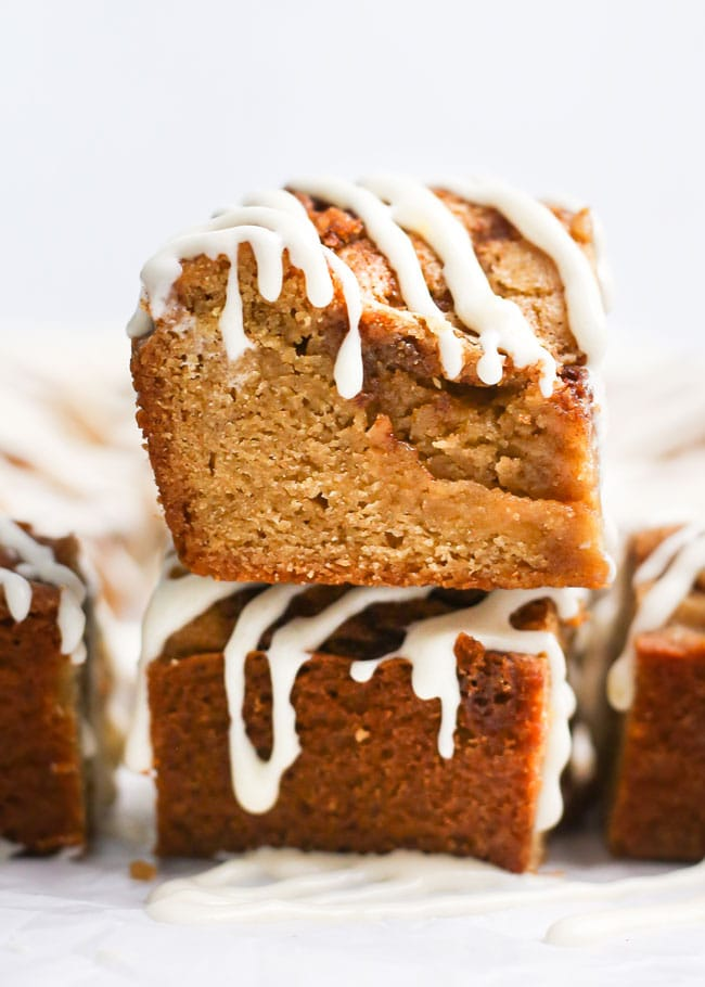 a stack of cinnamon roll blondies drizzled with cream cheese icing