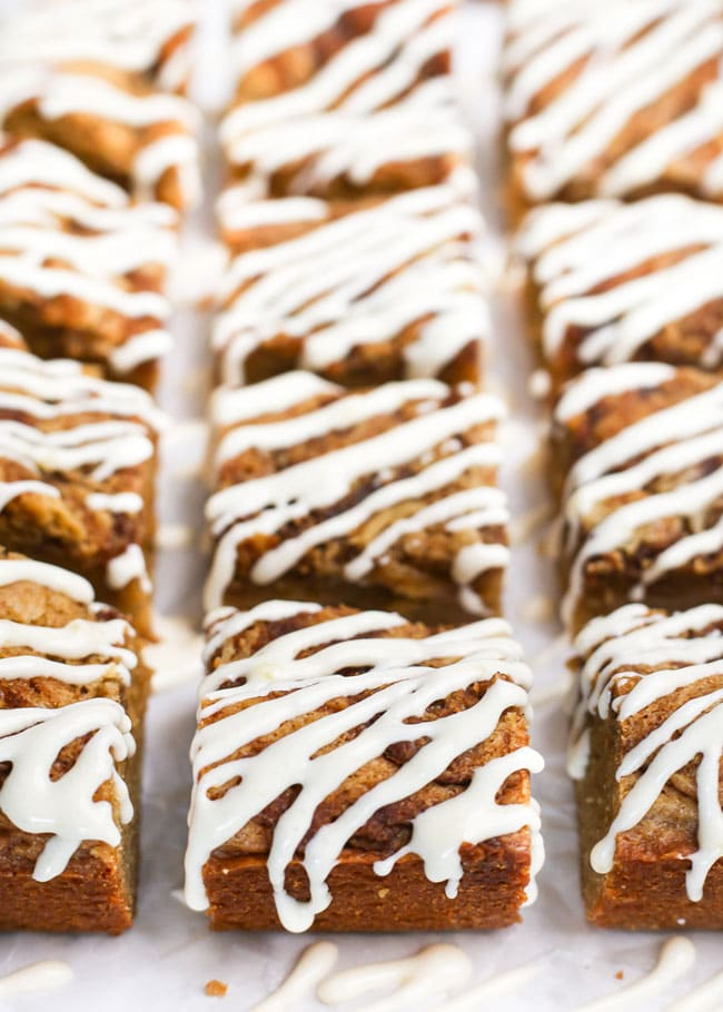 cinnamon roll blondies drizzled with cream cheese icing