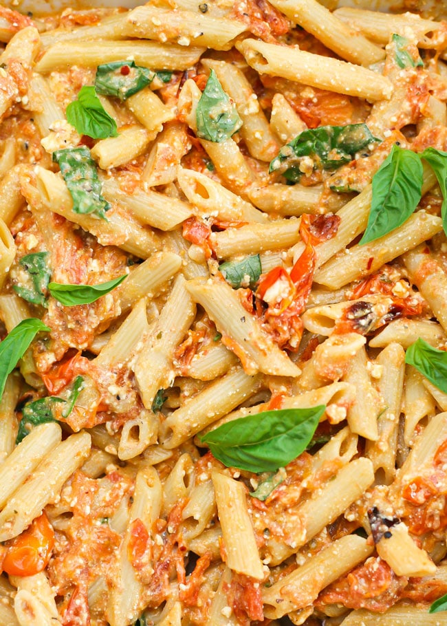 overhead photo of baked feta pasta topped with fresh basil