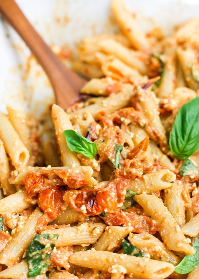a spatula mixing a dish of baked feta pasta