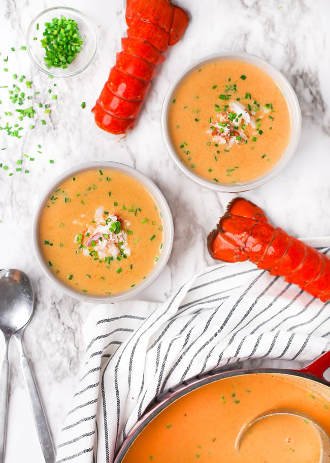 overhead photo of bowls of lobster bisque with spoons and lobster tails