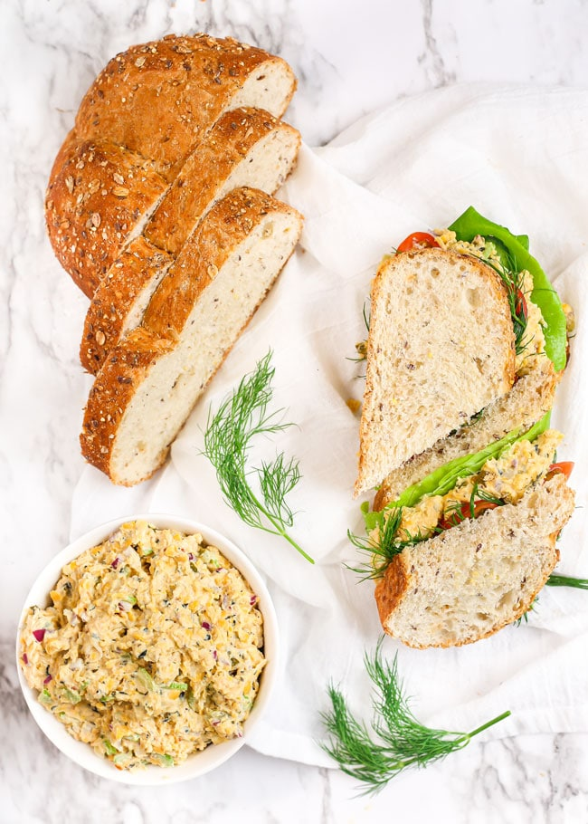 overhead photo of a no-tuna salad sandwich with a sliced loaf of bread and fresh dill