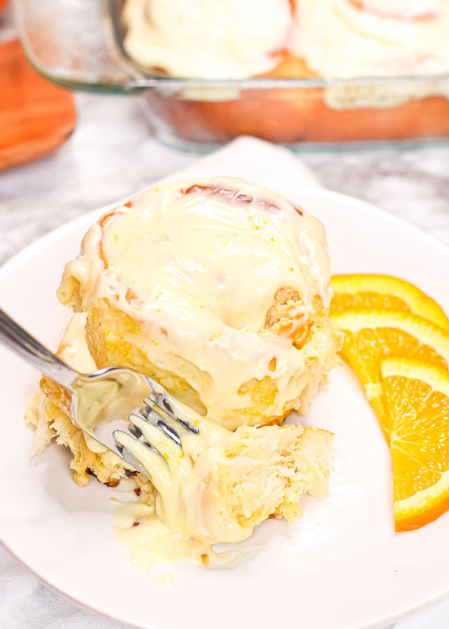 a fork digging into an orange roll topped with lots of cream cheese icing