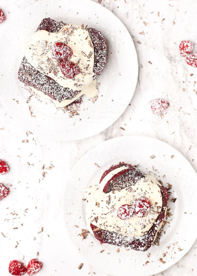 overhead photo of two plates of red velvet french toast topped with strawberries