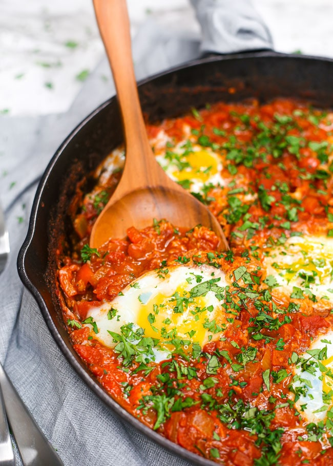 a spatula holding up a poached egg in a skillet of shakshuka