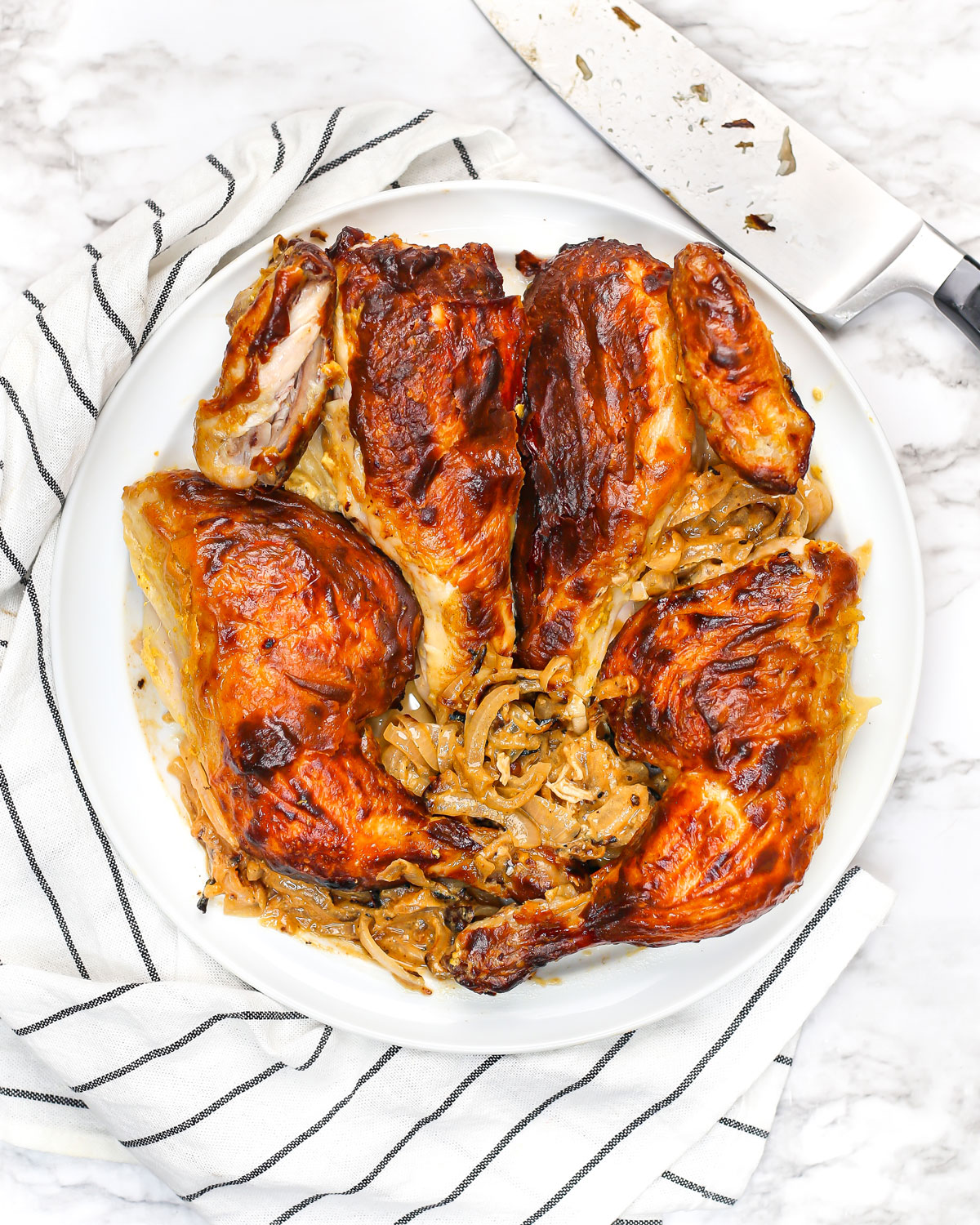 a whole roasted chicken quartered with onions