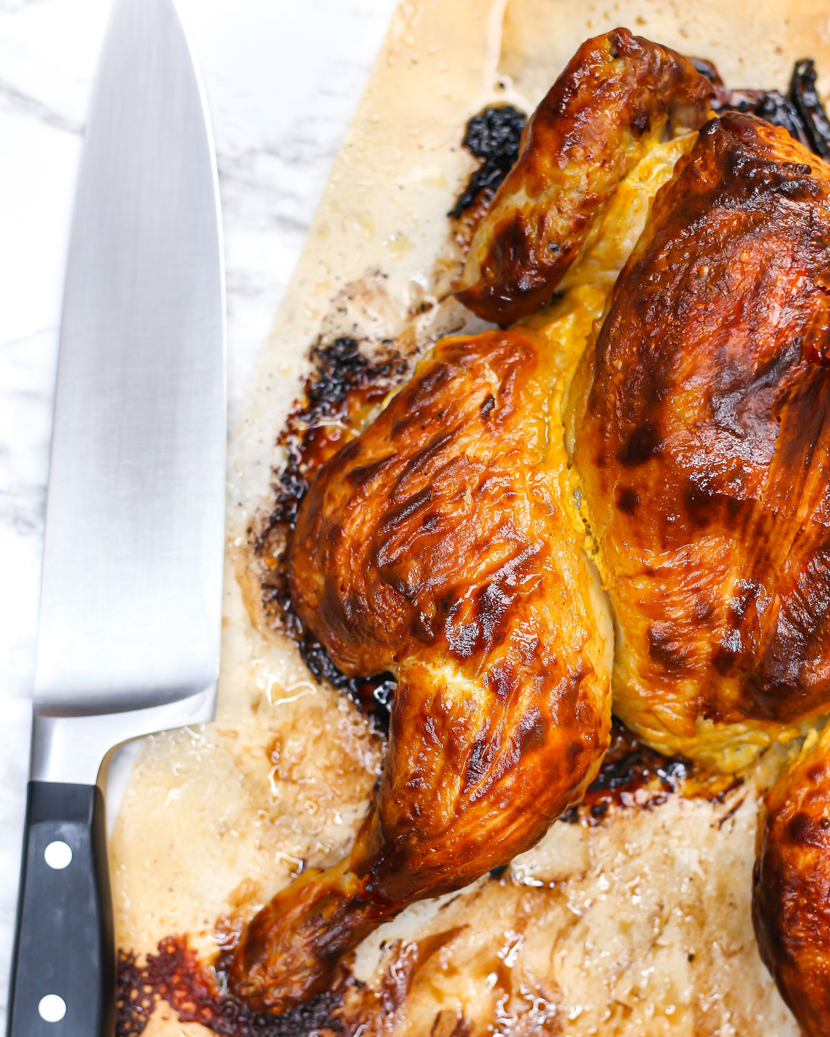 roasted spatchcock chicken on parchment paper with a chef's knife