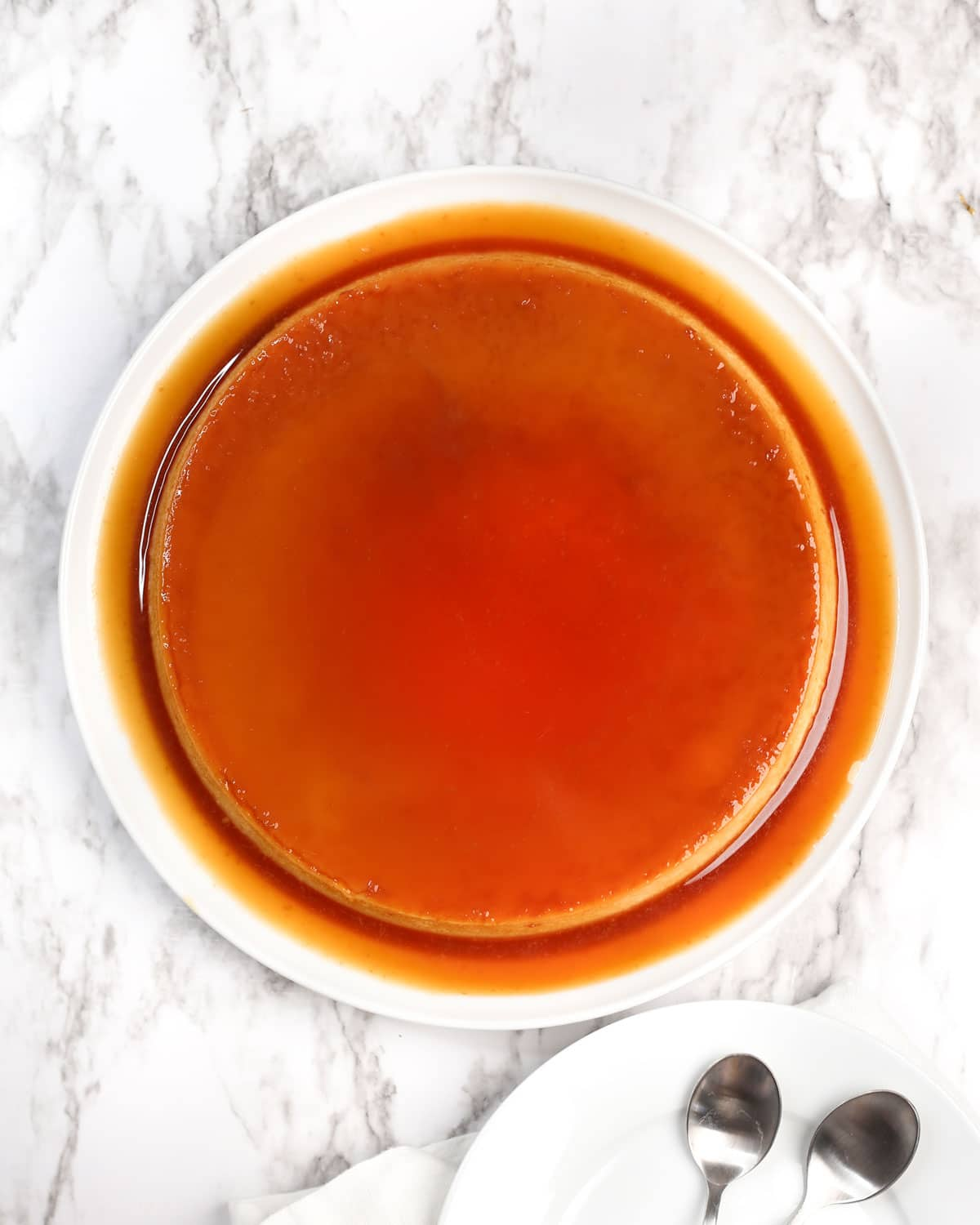 flan on a cake plate covered with caramel