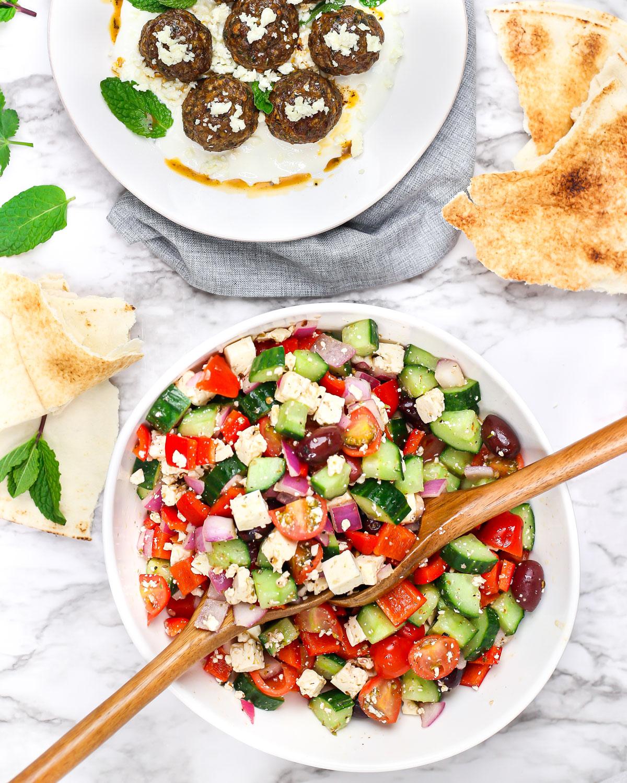 salad spoons tossing greek salad