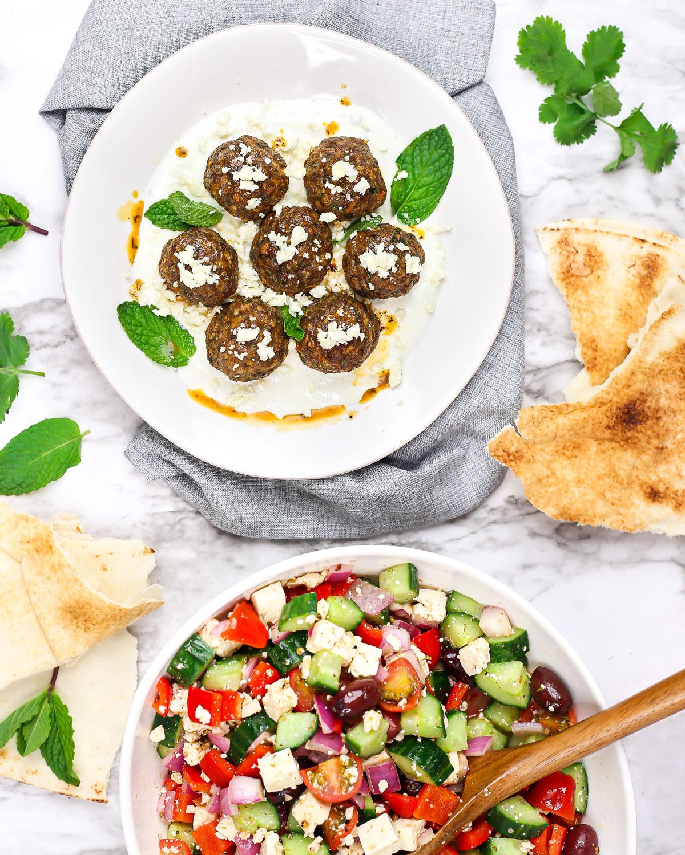 overhead photo of a plate of lamb meatballs with pita, feta, tzatziki, and Greek salad.