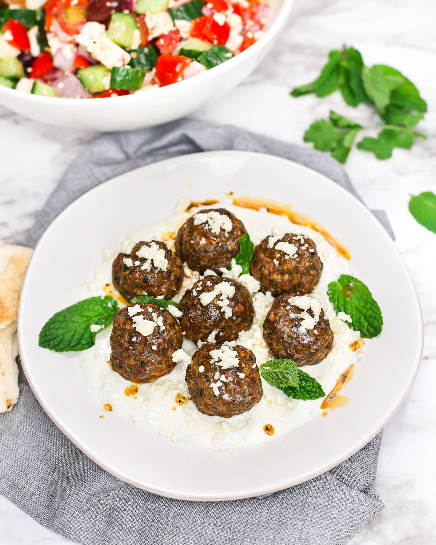 a plate of mediterranean lamb meatballs with tzatziki, feta, and fresh mint.