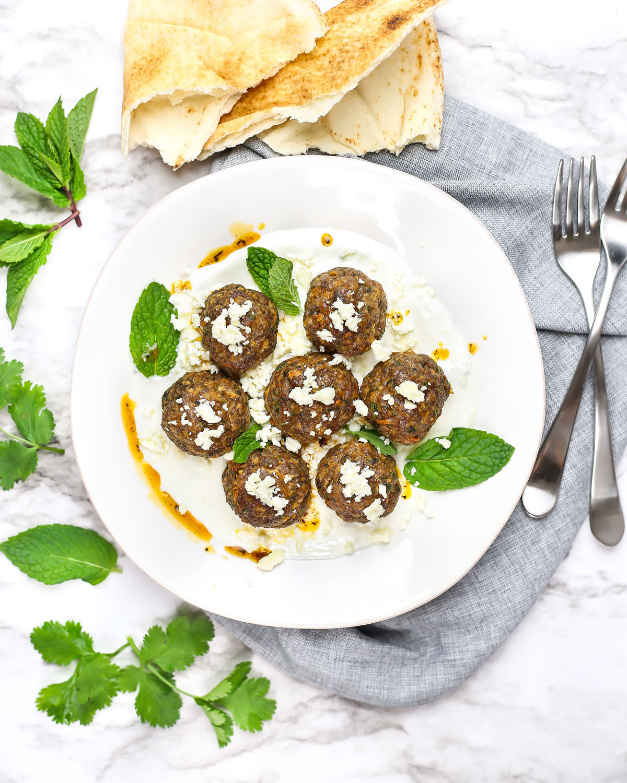 overhead photo of a plate of mediterranean lamb meatballs with tzatziki, feta, and pita