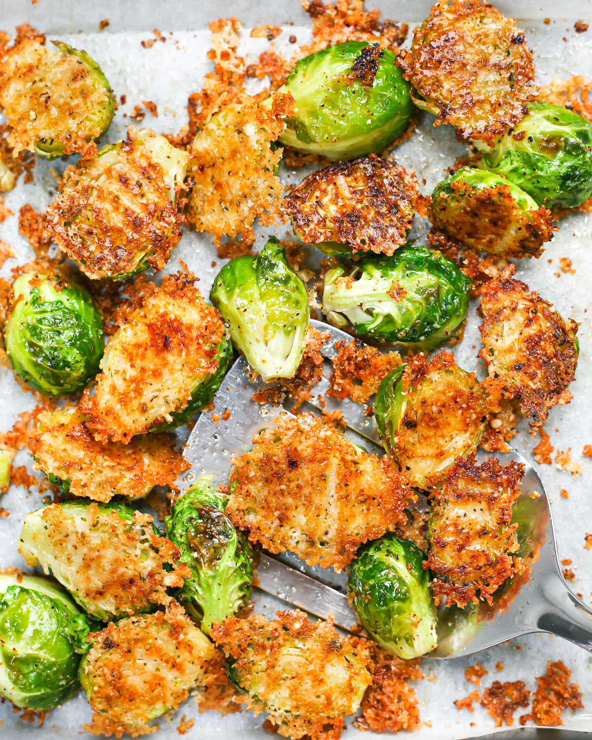 overhead photo of a spatula lifting parmesan roasted brussels sprouts from a sheet pan