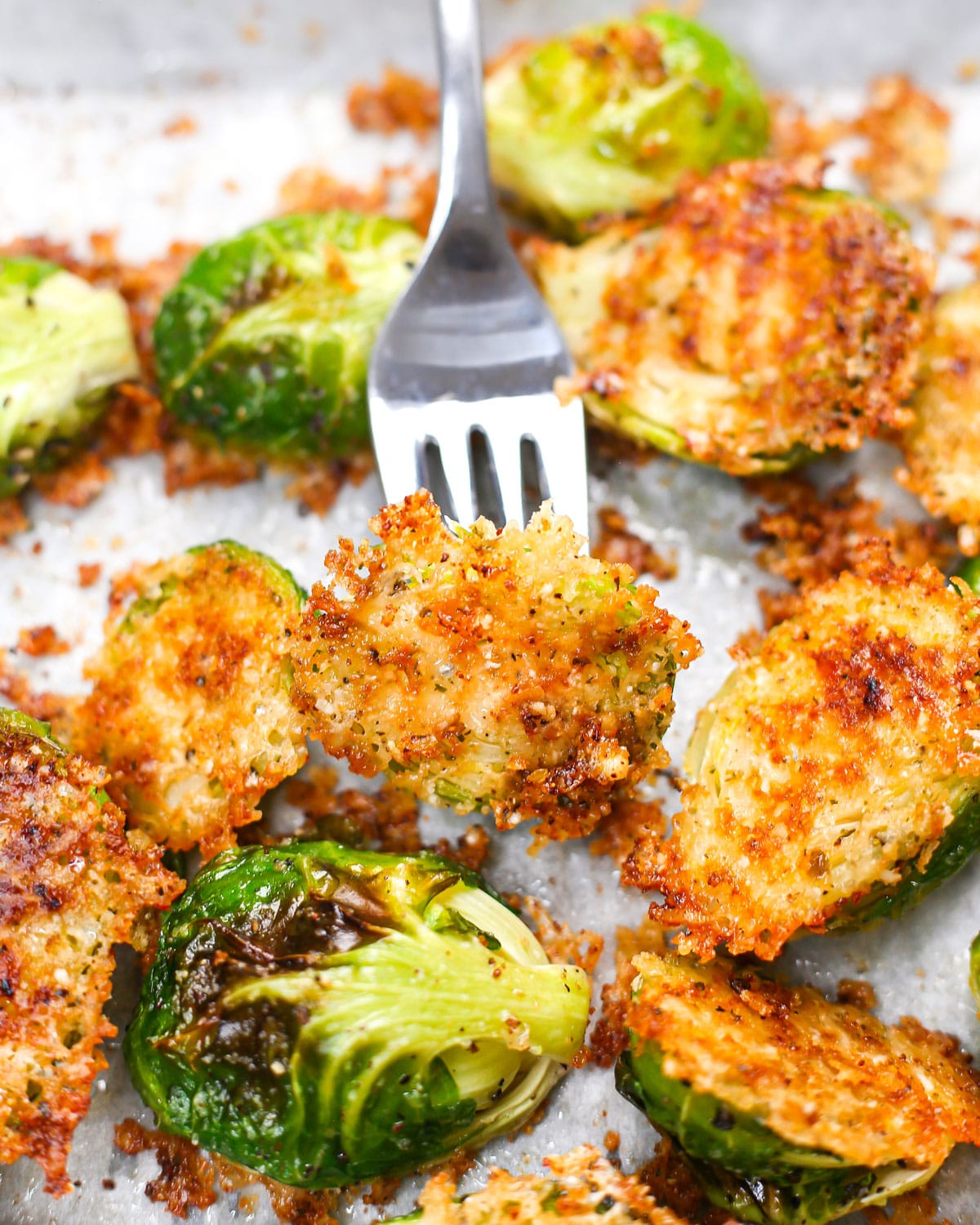 a fork lifting a roasted brussels sprout to show the crispy parmesan baked onto the bottom
