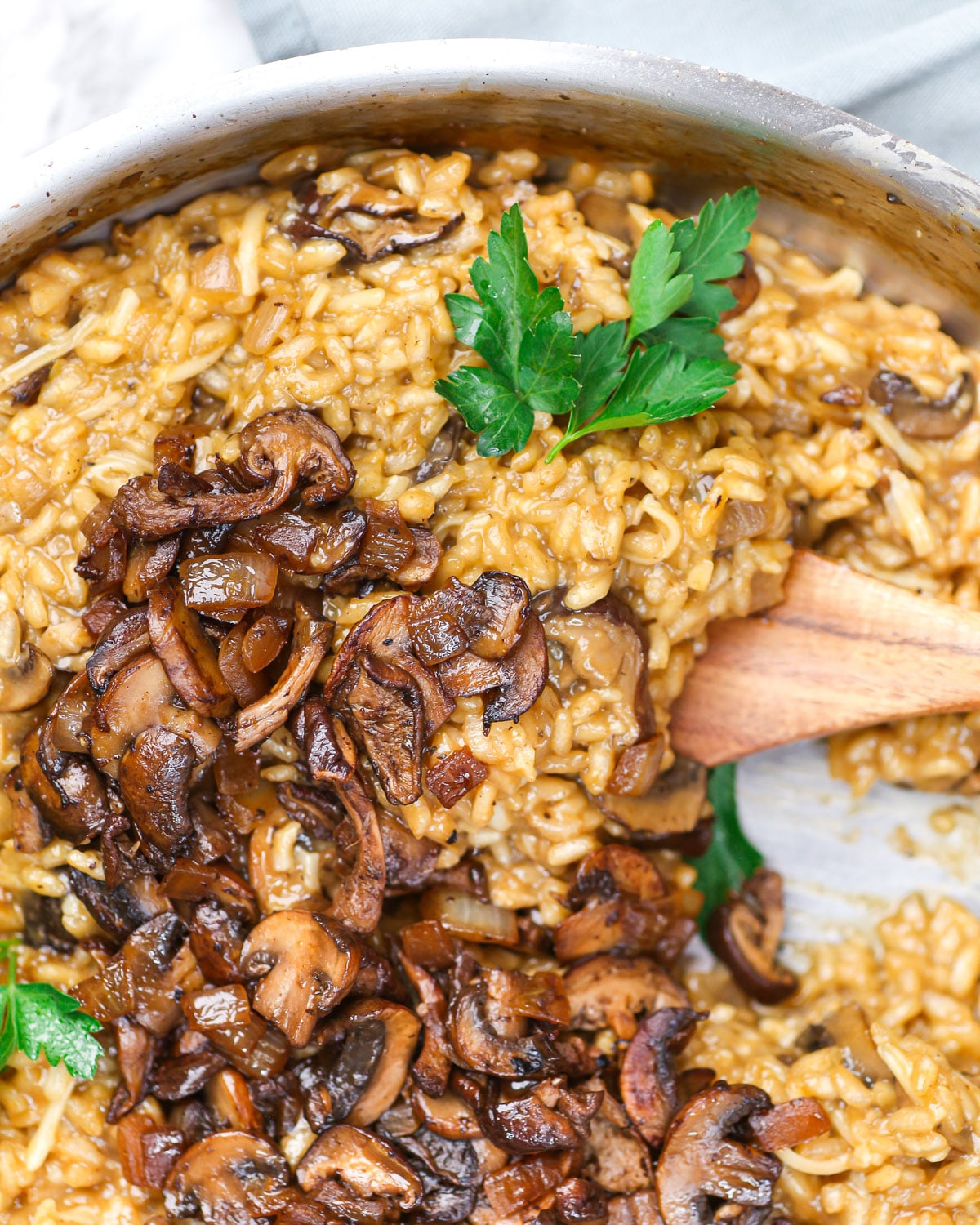 closeup of a spatula lifting vegan risotto topped with caramelized mushrooms