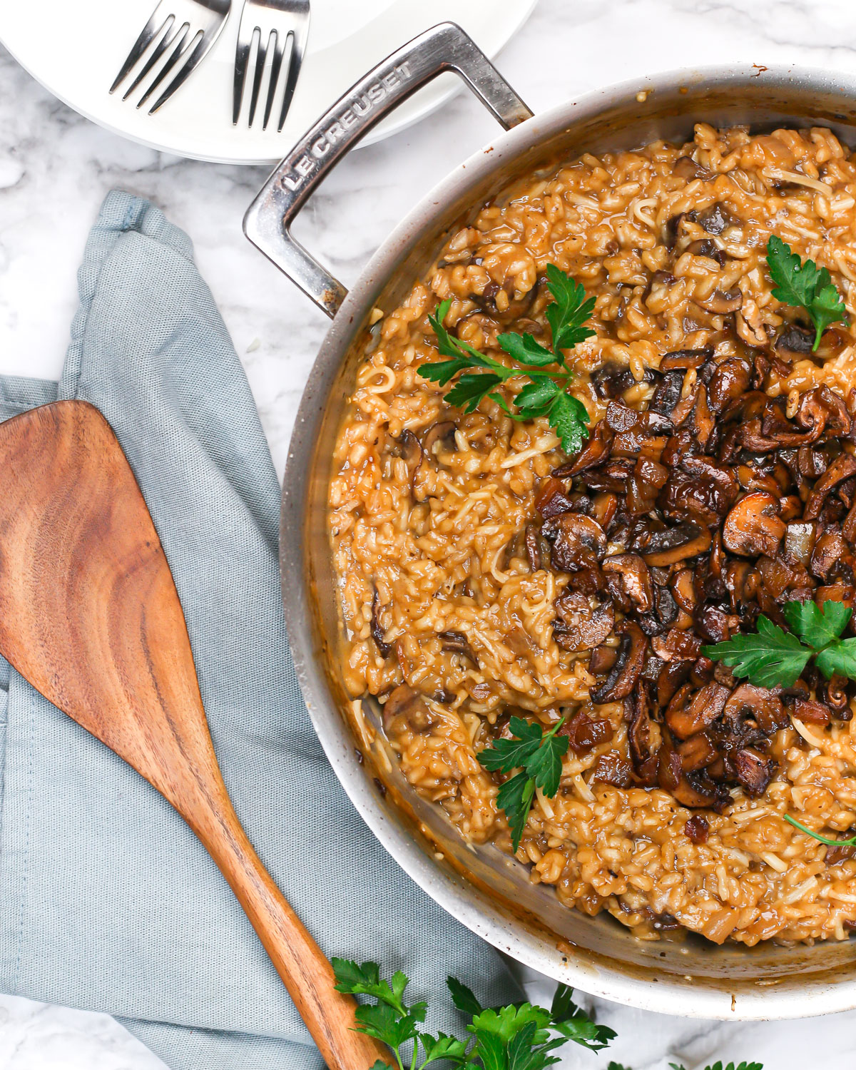 overhead photo of a skillet of vegan risotto topped with mushrooms and fresh parsley and with a spatula on the side