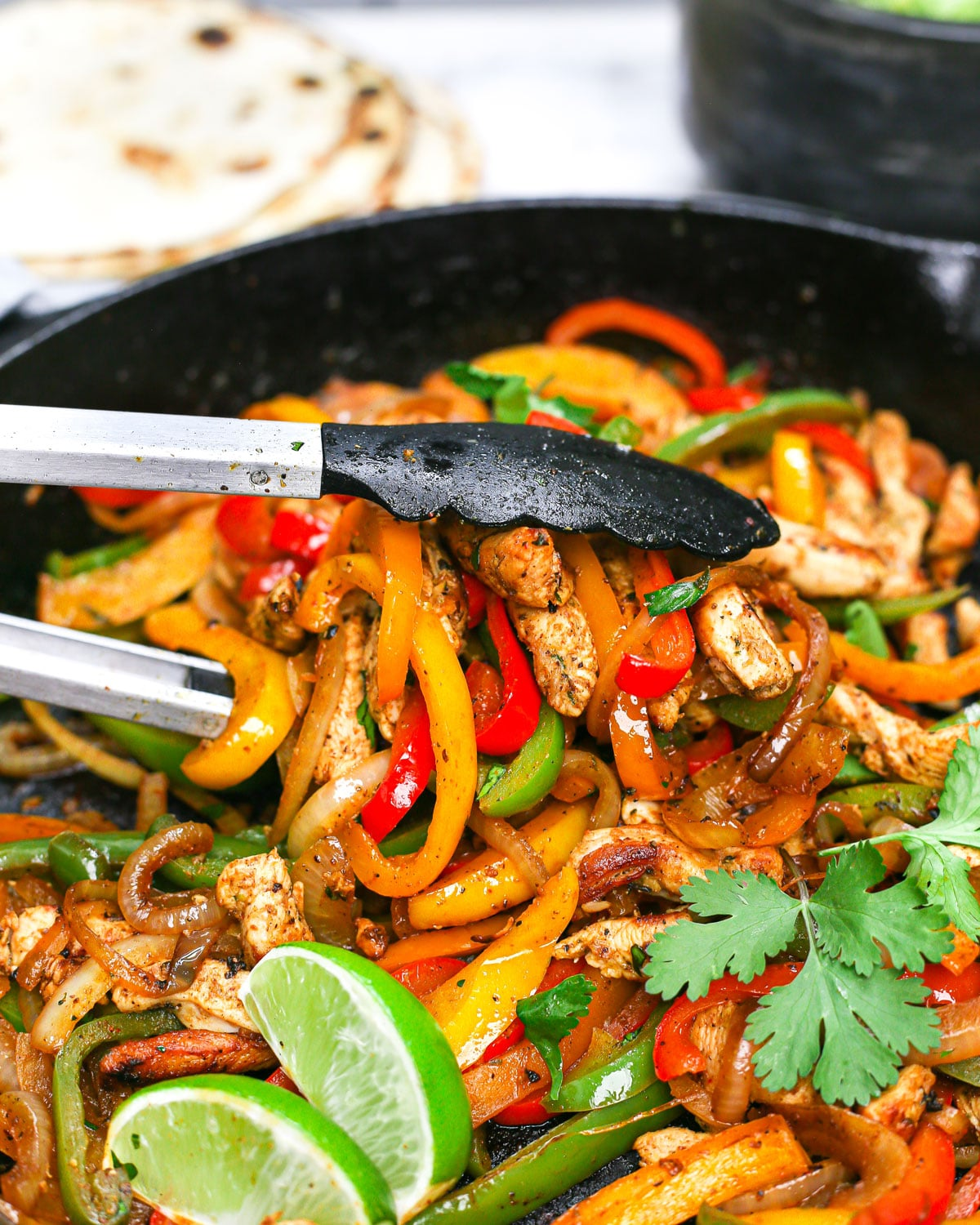 tongs picking up chicken fajtas from a skillet