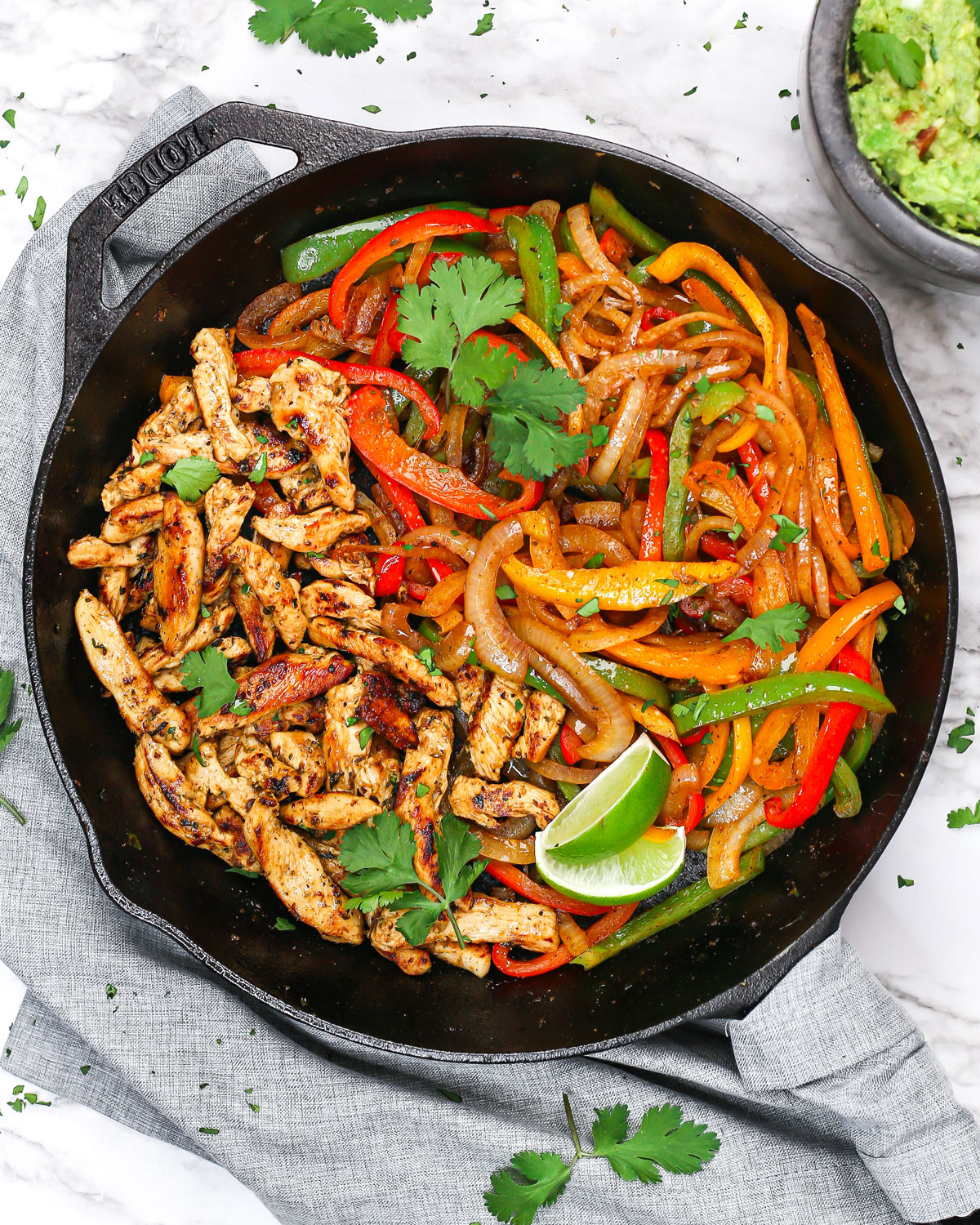chicken fajitas in a skillet with fresh lime wedges, cilantro, guacamole, and tortillas