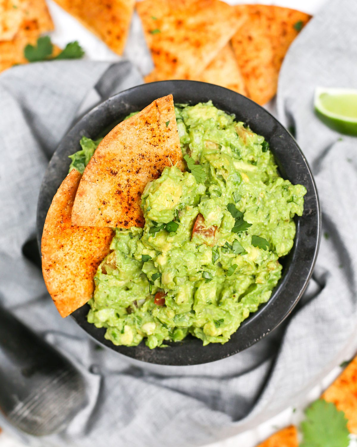 overhead photo of a bowl of guacamole with tortilla chips