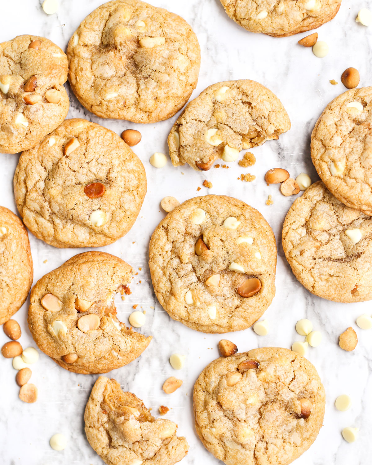 white chocolate macadamia nut cookies on marble with a bite taken from one