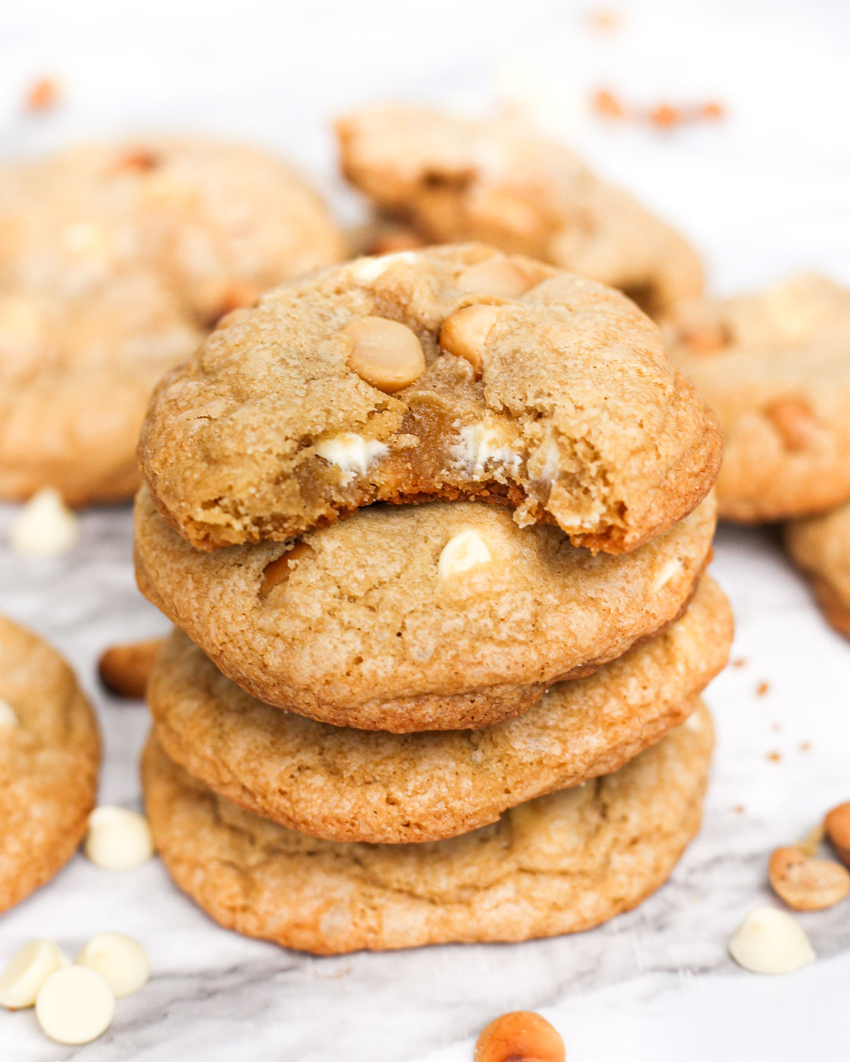 a stack of white chocolate macadamia nut cookies with a bite taken out of the top cookie