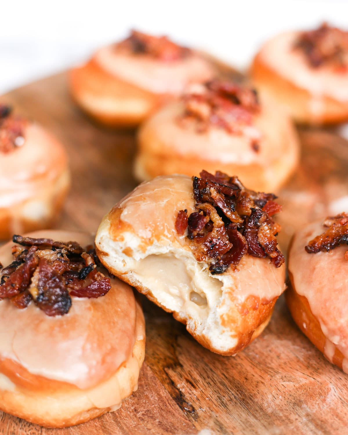a maple bacon donut with a bite taken from it exposing the custard inside