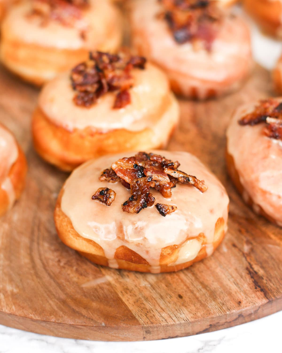 a maple bacon donut filled with custard on a platter