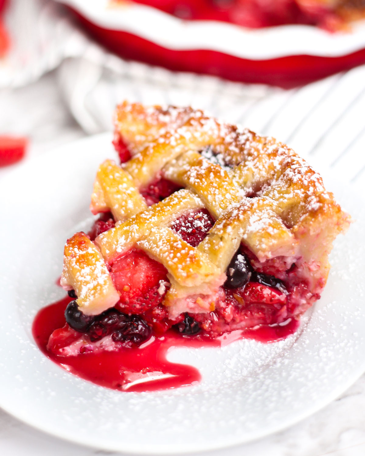 a slice of mixed berry pie served on a plate with powdered sugar
