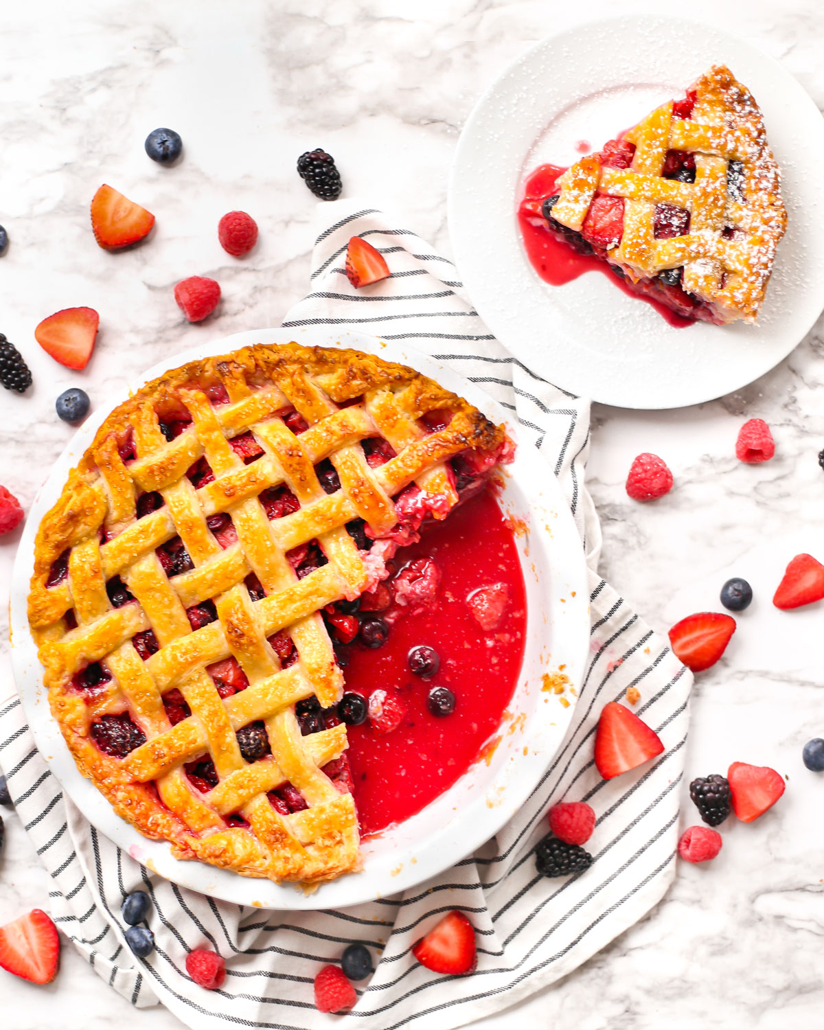 a mixed berry pie with a slice served on a plate
