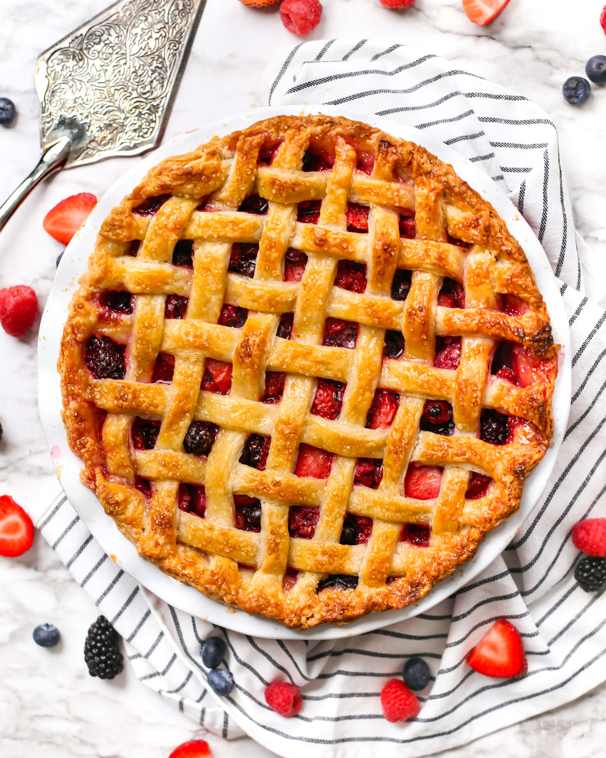 overhead photo of a mixed berry pie with a lattice-style top