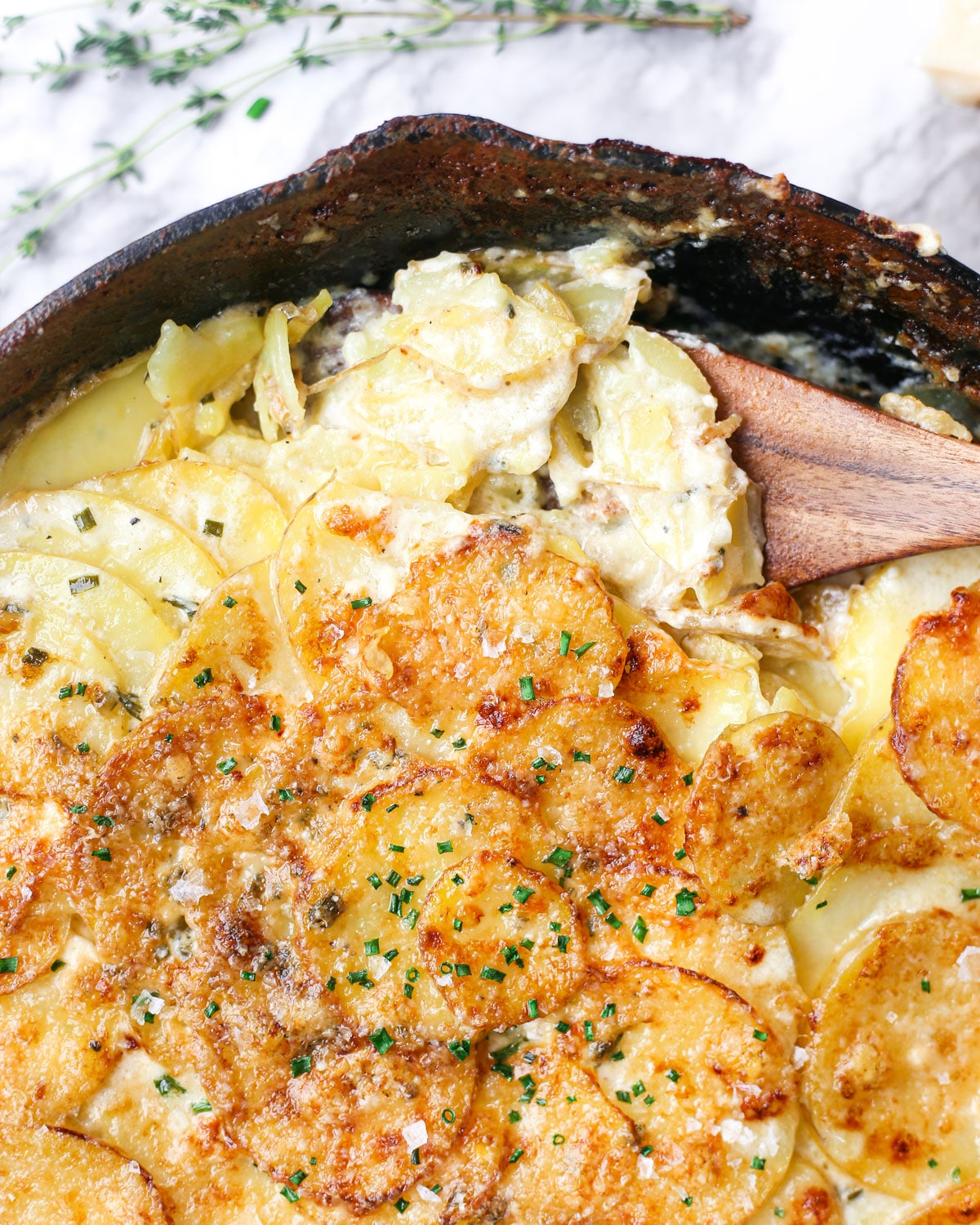 a spatula scooping au gratin potatoes from a skillet